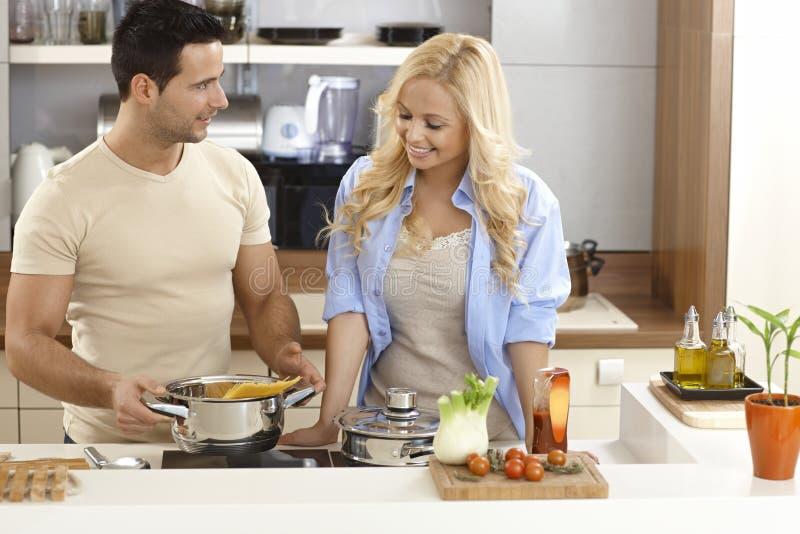 Jong paar die thuis koken royalty-vrije stock afbeelding