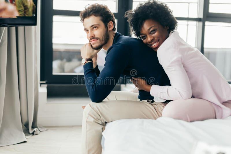Jong paar die tussen verschillende rassen en pret op bed ontspannen hebben Afrikaanse vrouw royalty-vrije stock afbeeldingen