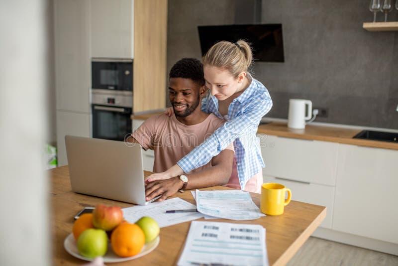 Jong paar die tussen verschillende rassen thuis laptop met behulp van die samen ontbijt hebben stock foto's