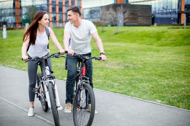 Jong paar die voor een fietsrit gaan op een zonnige dag in de stad stock fotografie