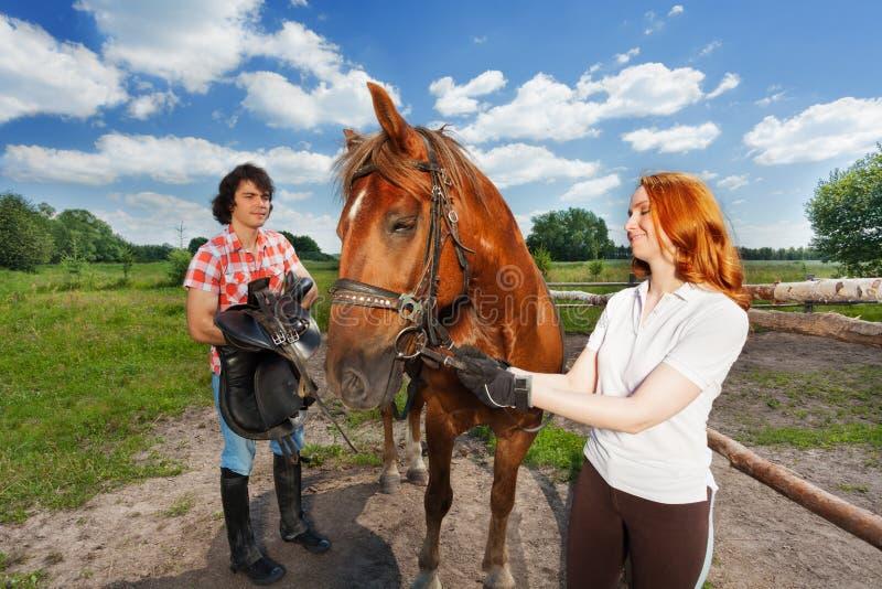 Jong paar die voor horseback rit bij landbouwbedrijf voorbereidingen treffen stock fotografie
