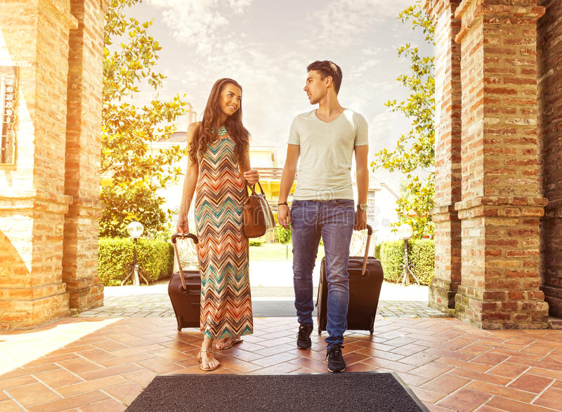 Jong paar die zich bij hotelgang op aankomst bevinden, zoekend ruimte, die koffers houden royalty-vrije stock foto