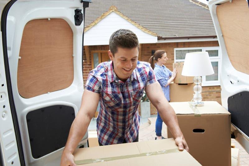Jong Paar die zich binnen aan Nieuwe Huis het Leegmaken Verwijderingsbestelwagen bewegen stock fotografie