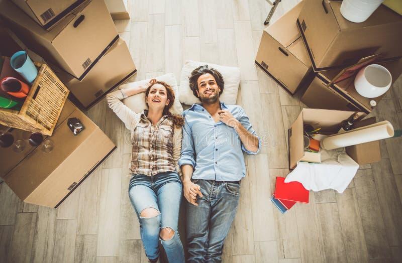 Jong paar die zich binnen in nieuwe flat bewegen stock afbeelding