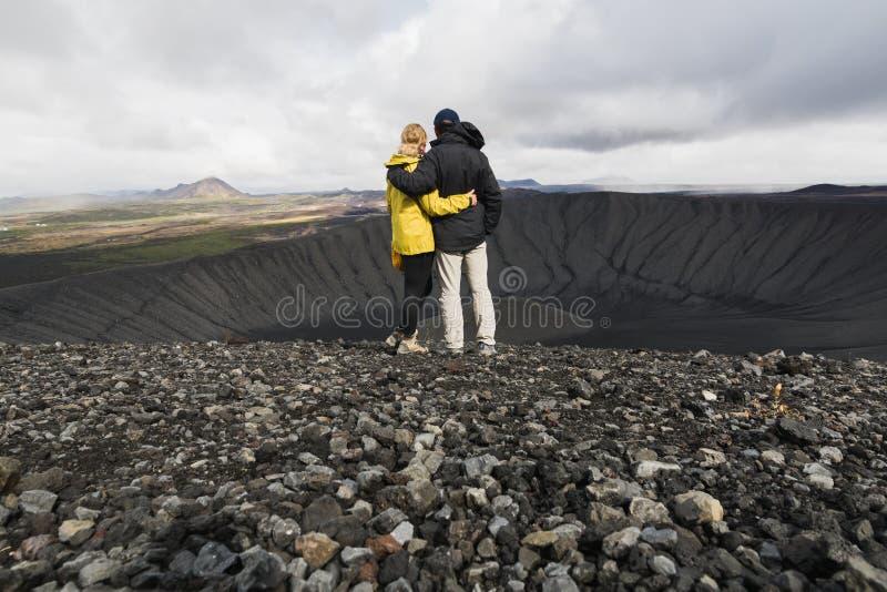 Jong paar die zich in de krater van Hverfjall-vulkaan op Myvatn-gebied bevinden, IJsland royalty-vrije stock afbeeldingen