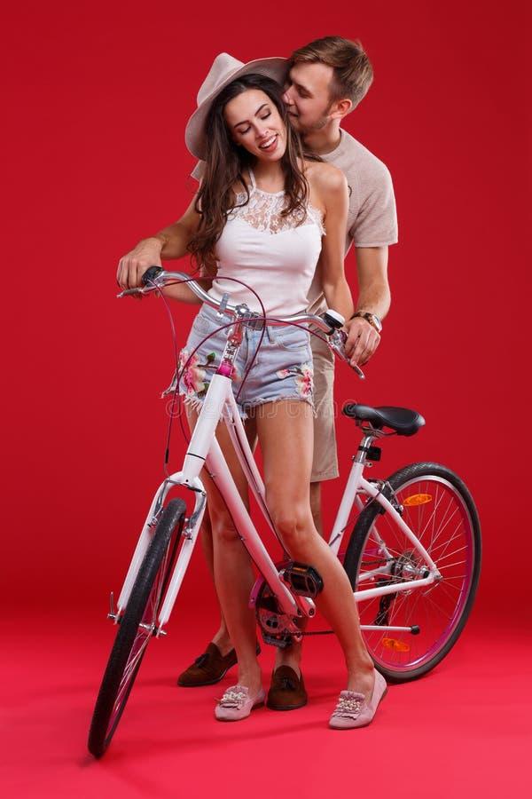 Jong paar die zich dichtbij fiets in studio op rode achtergrond bevinden royalty-vrije stock fotografie