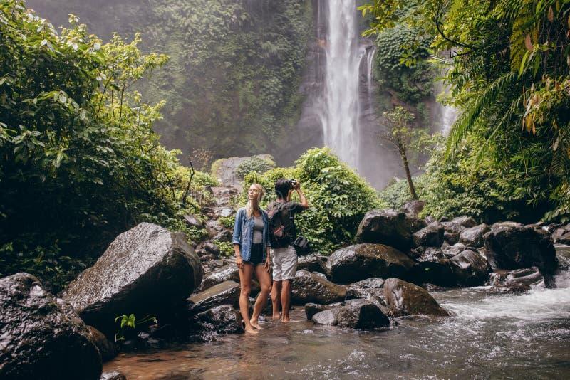 Jong paar die zich door de stroom dichtbij de waterval bevinden royalty-vrije stock fotografie