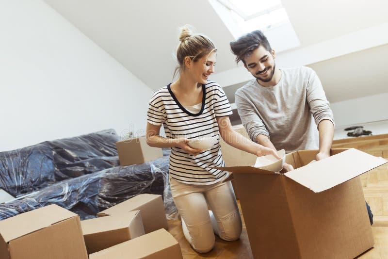 Jong paar die zich in hun nieuw huis bewegen stock foto's