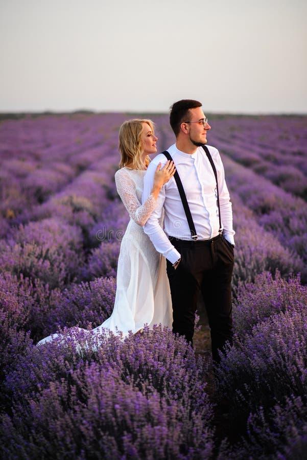 Jong paar die zich in midden van bloeiend lavendelgebied bij zonsopgang bevinden stock foto's