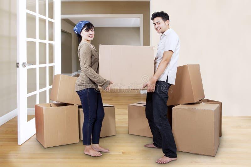 Jong paar die zich in nieuw huis bewegen stock foto
