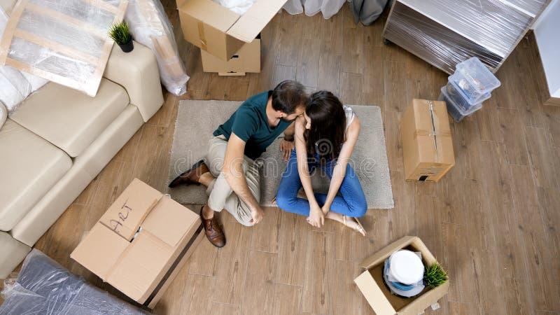 Jong paar die zich in nieuw huis en uitpakkende carboard dozen bewegen stock afbeelding