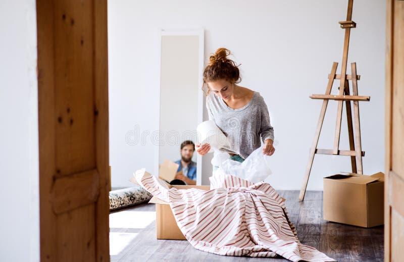 Jong paar die zich in nieuw huis, uitpakkende dozen bewegen stock foto