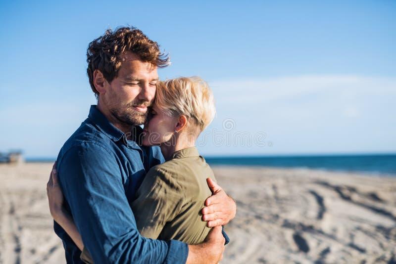 Jong paar die zich in openlucht op strand, het koesteren bevinden De ruimte van het exemplaar royalty-vrije stock afbeeldingen