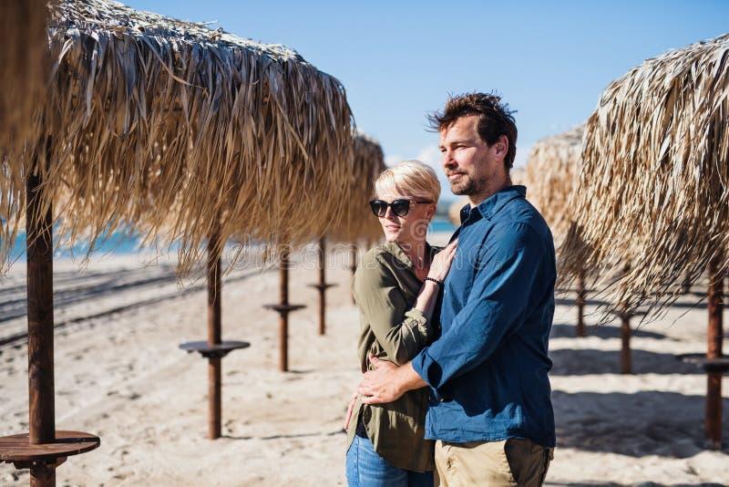 Jong paar die zich in openlucht op strand, het koesteren bevinden De ruimte van het exemplaar royalty-vrije stock afbeelding