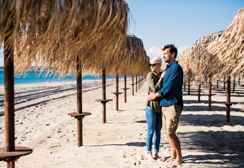 Jong paar die zich in openlucht op strand, het koesteren bevinden De ruimte van het exemplaar royalty-vrije stock foto