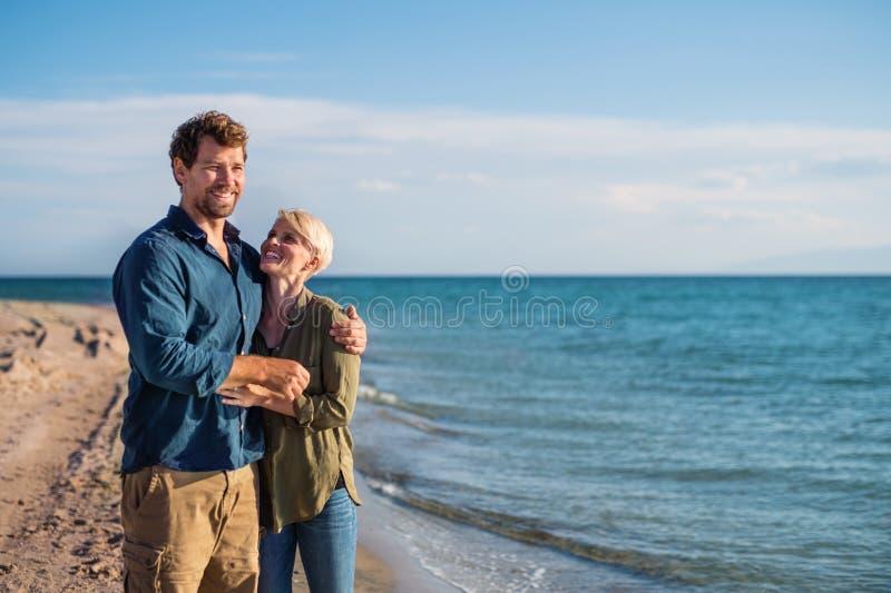 Jong paar die zich in openlucht op strand, het spreken bevinden De ruimte van het exemplaar royalty-vrije stock foto's