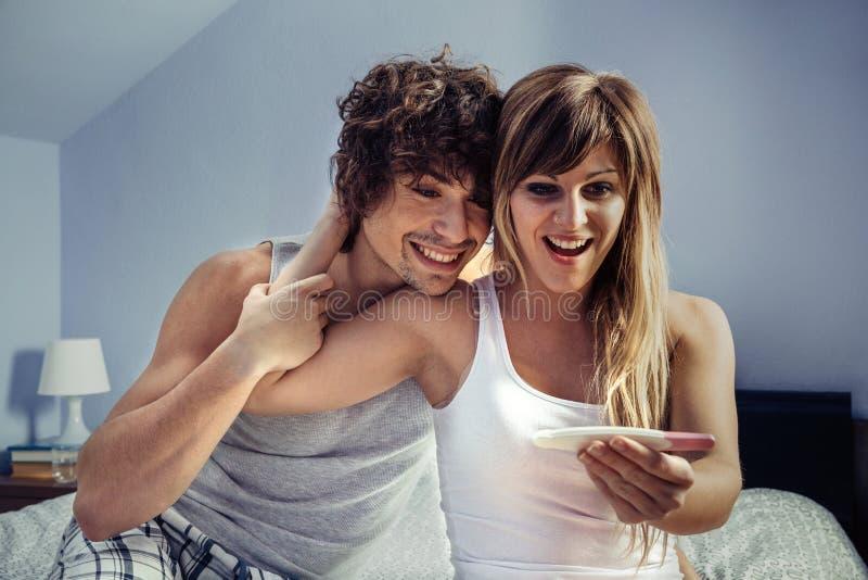 Jong paar die zwangerschapstest in slaapkamer kijken royalty-vrije stock foto's