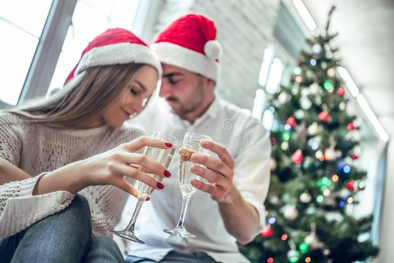 _jong paar drinken champagne, kijken bij elkaar en glimlachen; dichtbij de Kerstmisboom thuis stock fotografie