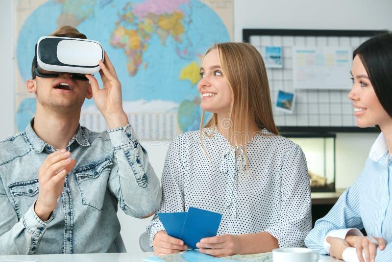 Jong paar in een communicatie van het reisagentschap met een virtuele opgewekte de werkelijkheidshoofdtelefoon van het reisbureau stock foto's