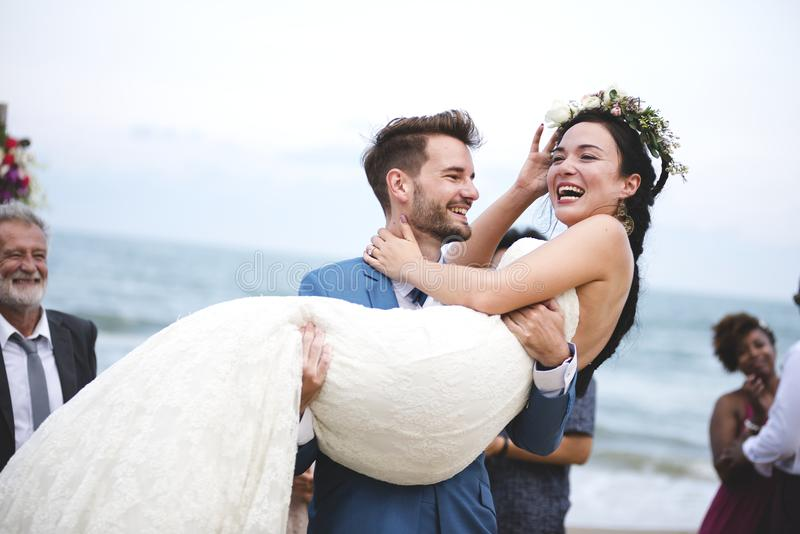 Jong paar in een huwelijksceremonie bij het strand royalty-vrije stock afbeelding