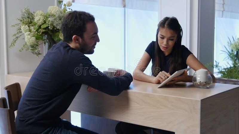 Jong paar in een koffie die iets bespreken die digitale tablet bekijken royalty-vrije stock foto