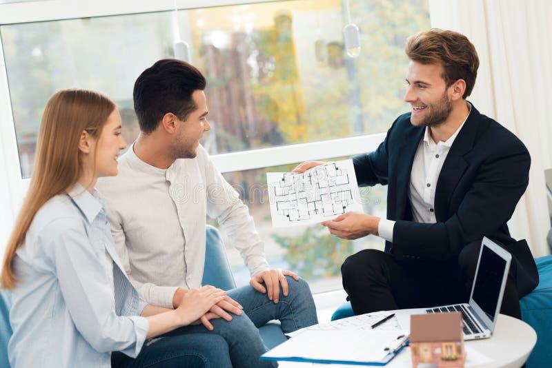 Jong paar in een vergadering met een makelaar in onroerend goed De kerel en het meisje maken een contract met makelaar in onroere stock fotografie
