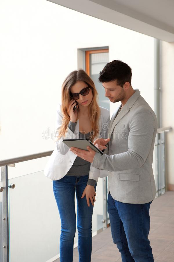 Jong paar in gang met tablet en mobiel royalty-vrije stock fotografie