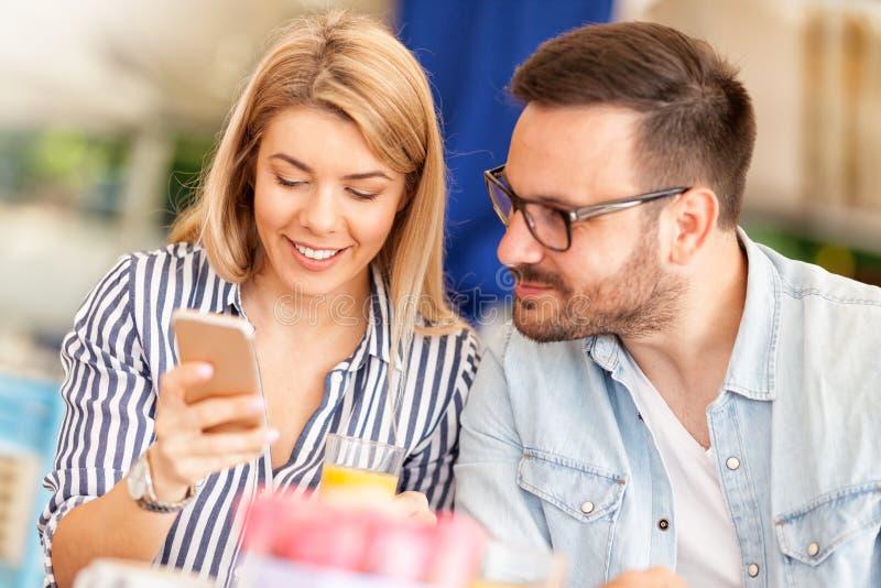 Jong paar geinteresseerd in het bekijken smartphone stock foto's
