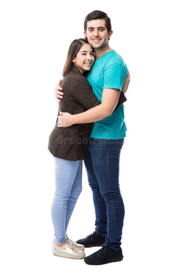 Jong paar geknuffel in een omhelzing stock foto's