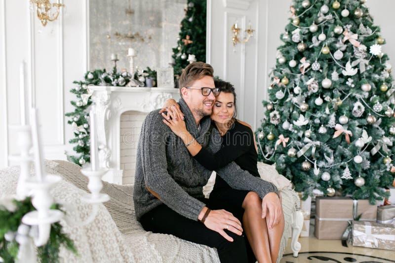 Jong Paar Gelukkige familie die pret heeft thuis Kerstmisochtend in heldere woonkamer Gelukkig Nieuwjaar verfraaid stock afbeeldingen