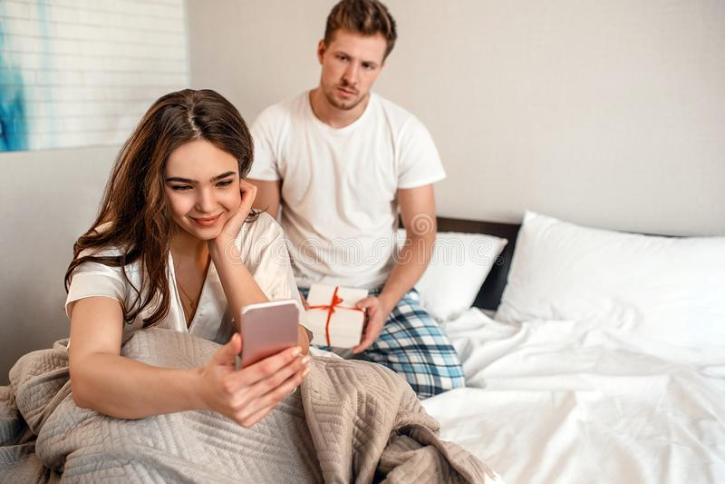 Jong paar in het bed De glimlachende onverschillige vrouw met haar telefoon negeert de haar ongelukkige mens met een gift stock foto's
