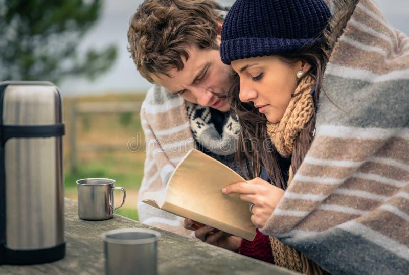 Jong paar in het kader van algemeen lezingsboek in openlucht in een koude dag stock afbeelding