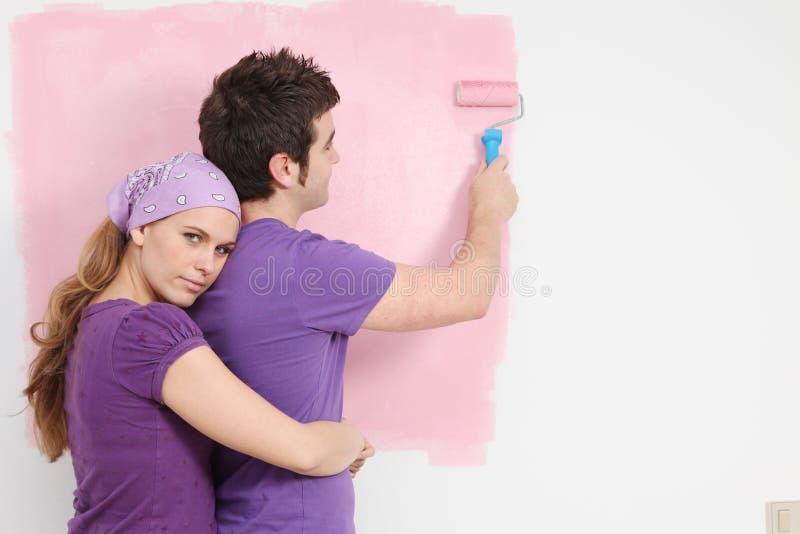 Jong paar het schilderen babykinderdagverblijf in nieuw huis royalty-vrije stock afbeeldingen
