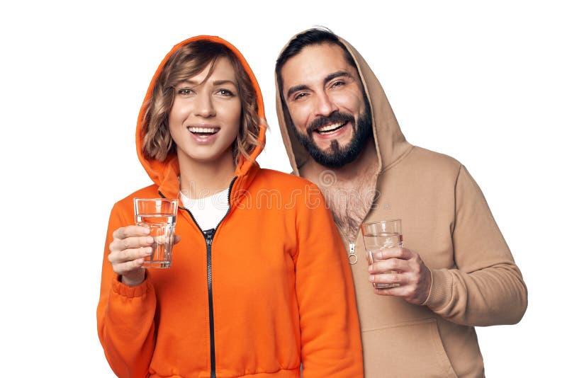 Jong paar in huiskleren met glas water royalty-vrije stock afbeelding