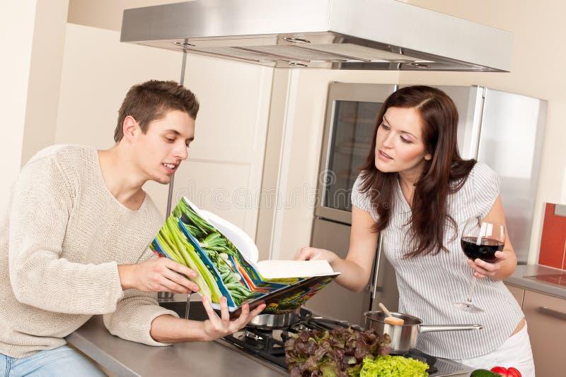 Jong paar in keuken met kookboek stock afbeelding