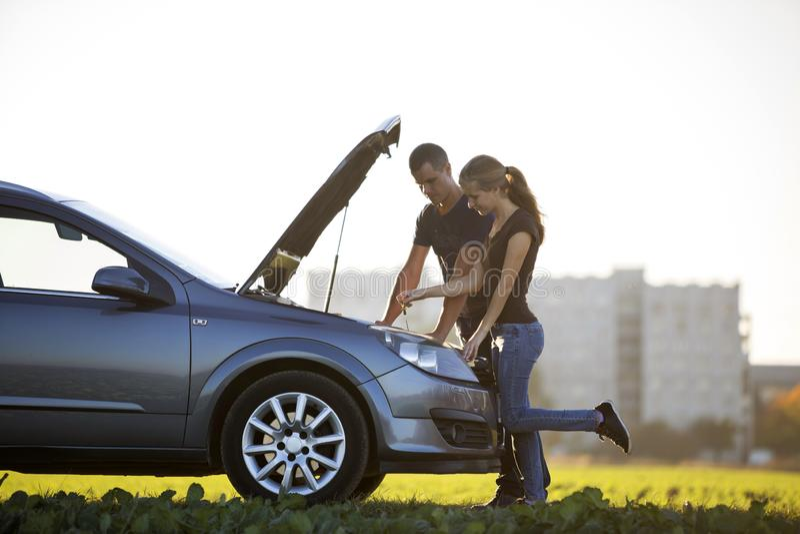 Jong paar, knappe man en aantrekkelijke vrouw bij auto met popp stock afbeelding