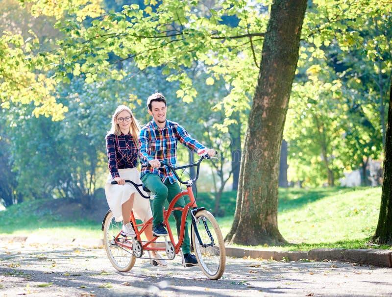 Jong paar, knappe man en aantrekkelijke vrouw op fiets achter elkaar in zonnig de zomerpark of bos royalty-vrije stock fotografie