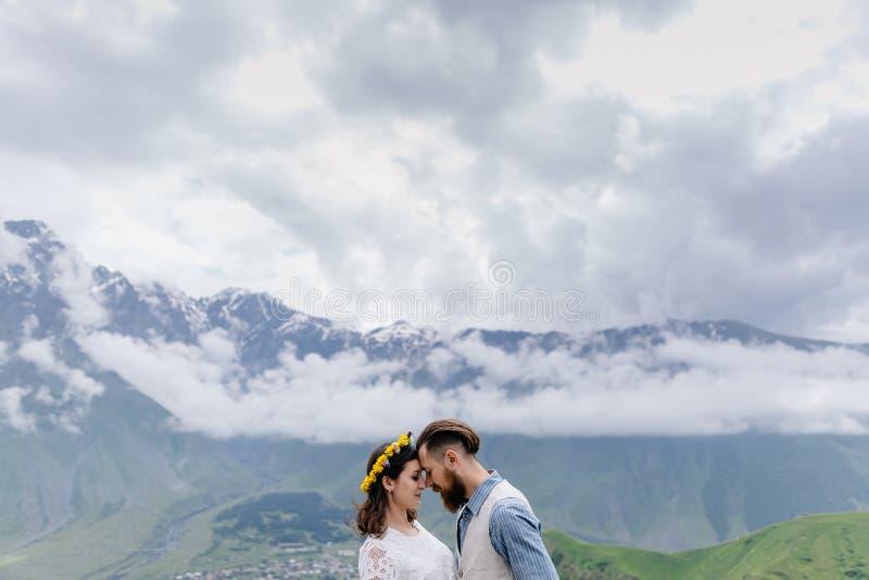 Jong paar in liefde, die elkaar, een mens in een kostuum en meisje in wit met bloemen bekijken, die zich in openlucht bevinden royalty-vrije stock foto's