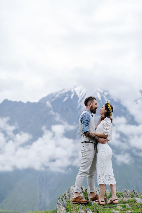 Jong paar in liefde, die elkaar, een mens in een kostuum en meisje in wit met bloemen bekijken, die zich in openlucht bevinden royalty-vrije stock fotografie