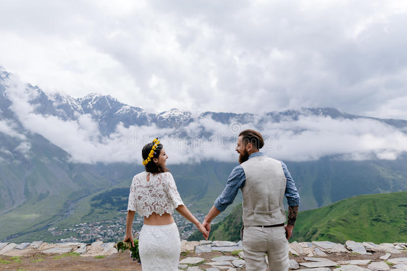 Jong paar in liefde, die elkaar, een mens in een kostuum en meisje in wit met bloemen bekijken, die zich in openlucht bevinden stock afbeeldingen