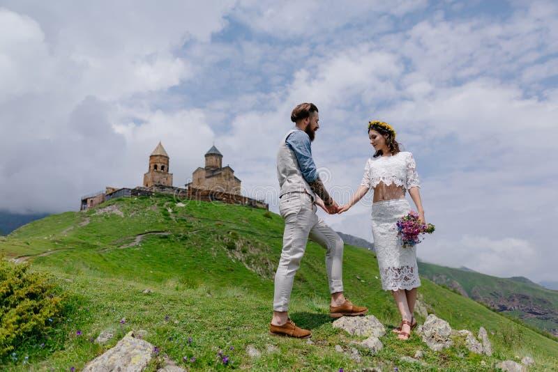 Jong paar in liefde, die handen, de mens in kostuum en meisje in wit met bloemen houden stock foto