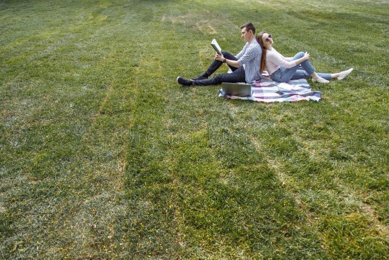Jong paar in liefde die op het gazon na studie rusten De ruimte van het exemplaar stock fotografie