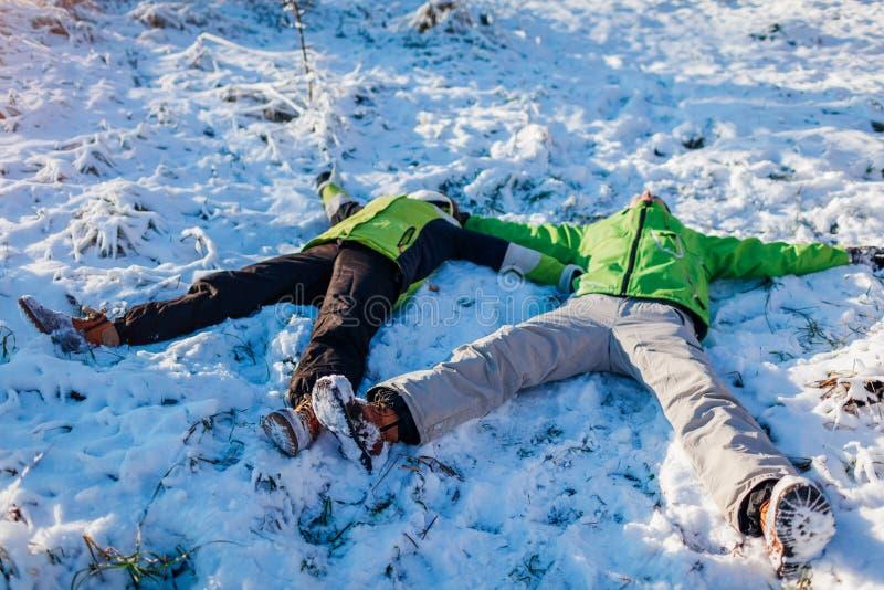 Jong paar in liefde die in sneeuw liggen en sneeuwengelen maken Mensen die pret in de winterbos hebben royalty-vrije stock fotografie