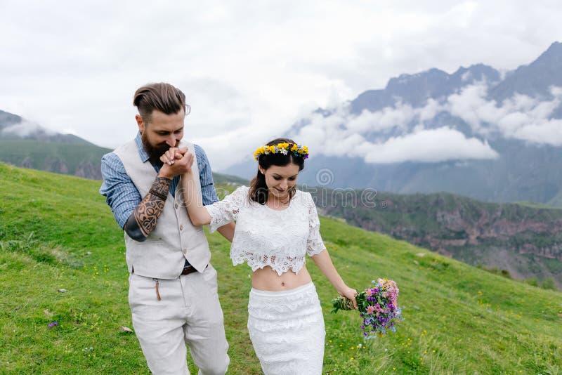Jong paar in liefde, geknuffel, een mens in een kostuum en meisje in wit met bloemen, royalty-vrije stock foto's