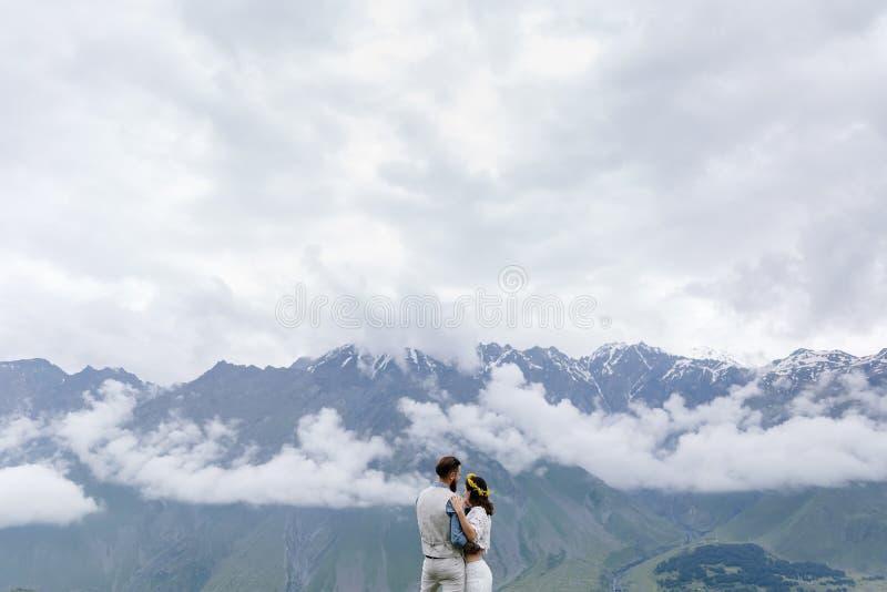 Jong paar in liefde, geknuffel, een mens in een kostuum en meisje in wit met bloemen, stock fotografie