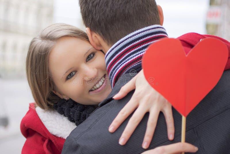 Jong paar in liefde het koesteren Meisjeholding Rood Hart en het Glimlachen Het concept van de Dag van valentijnskaarten stock foto's