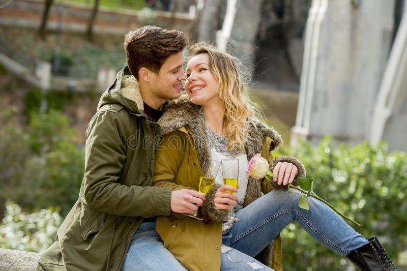 Jong paar in liefde het kussen teder op straat het vieren Valentijnskaartendag of verjaardag die in Champagne toejuichen royalty-vrije stock fotografie