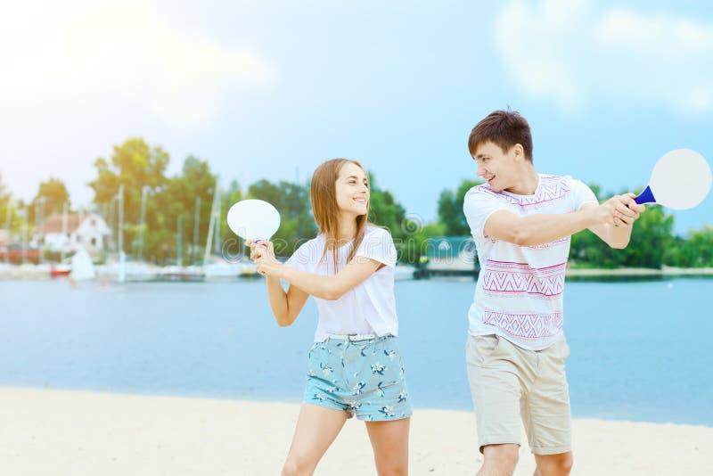 Jong paar in liefde het spelen met matkotrackets stock afbeeldingen