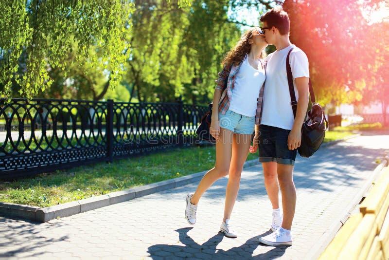 Jong paar in liefde kussen die in stadspark bij de zomer lopen stock foto