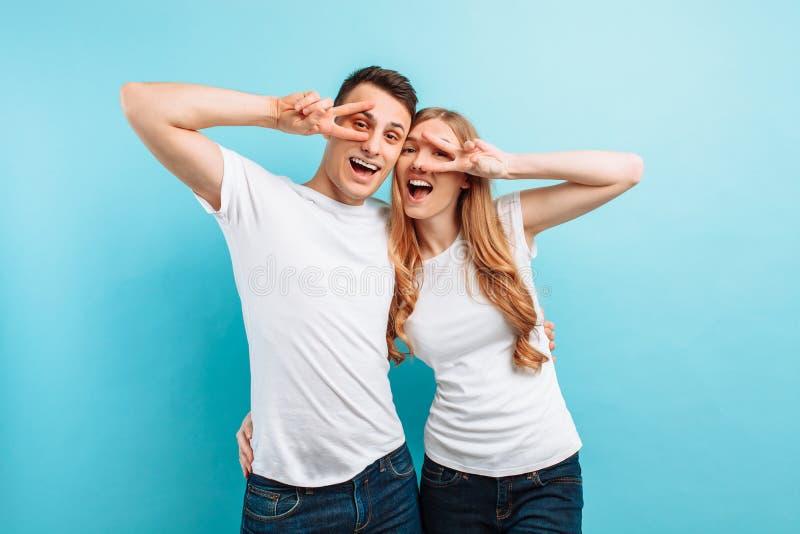 Jong paar in liefde, man en vrouw die, die en een gebaar met twee vingers, op lichtblauwe achtergrond verheugen zich tonen royalty-vrije stock foto